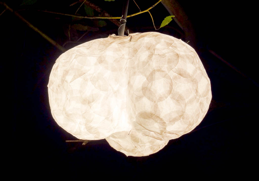 Lamp-shade made out of heat-resistant confetti, litten by an halogen bulb.